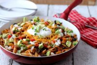 Red Skillet Containing Cooked Chicken, Pasta, Black Beans and Salsa topped with Sour Cream