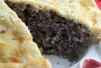 Tourtiere, French Meat pie with a slice removed revealing the filling inside.